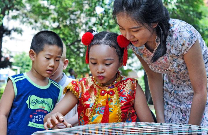 Jovens familiarizam-se com instrumentos musicais chineses numa feira de gastronomia, arte e culturas moçambicana e chinesa onde juntou hoje centenas de pessoas na capital moçambicana, num evento organizado por estudantes de Moçambique graduados na China, Maputo, Moçambique, 23 de fevereiro de 2019.