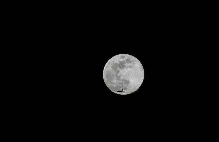 Um avião cruza o seu caminho com a Lua Cheia, sobre Lisboa. 29 de abril de 2018. MIGUEL A. LOPES/LUSA