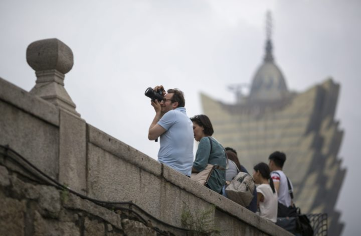 epa05292988 A tourist takes photographs near the ruins of Saint Paul's as the Grand Lisboa Casino stands in the background in Macau, China, 06 May 2016 (issued 07 May 2016). Macau, once a popular destination for mainland gamblers, launched in April an ambitious five-year plan to increase tourism revenues and to reduce the economy's reliance on gaming.  EPA/JEROME FAVRE