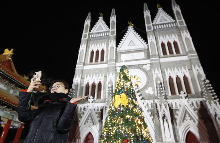 epa07247731 Catholic takes photo beside the Xishiku Catholic Church in Beijing, China, 25 December 2018. Catholics in China attend church masses as they prepare to celebrate the religious holiday to commemorate the birth of Christ.  EPA/WU HONG