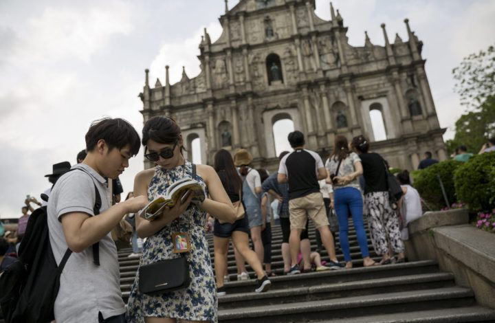 epa05292743 Tourists read a map in front of Saint Paul's ruins in the historic center of the city in Macau, China, 06 May 2016 (issued 07 May 2016). The ruins dates back to the 16th century and were listed in 2005 as part of the Historic Centre of Macau, a UNESCO World Heritage Site. Macau, once a popular destination for mainland gamblers, launched in April an ambitious five-year plan to increase tourism revenues and to reduce the economy's reliance on gaming.  EPA/JEROME FAVRE