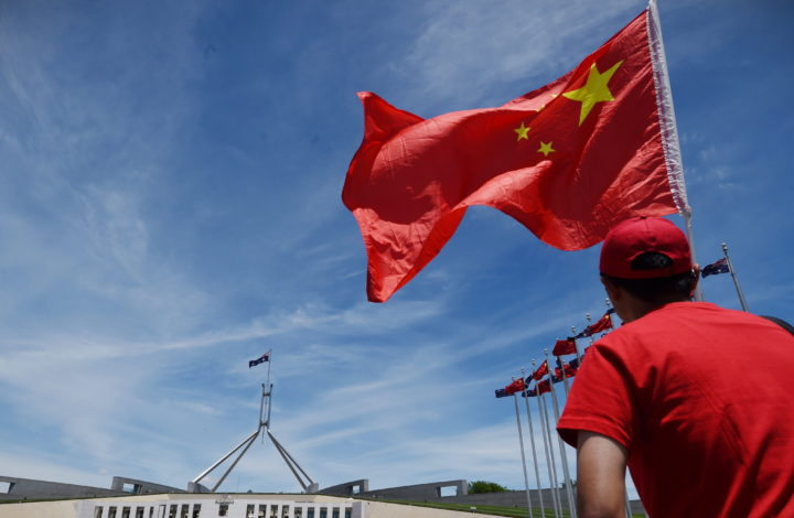 epa08024716 (FILE) - A Chinese government supporter waves a Chinese flag outside Parliament House in Canberra, Australia, 17 November 2014 (reissued 25 November 2019. According to media reports, Australian authorities are investigating an alleged Chinese attempt to plant a spy into parliament.  EPA/LUKAS COCH  AUSTRALIA AND NEW ZEALAND OUT