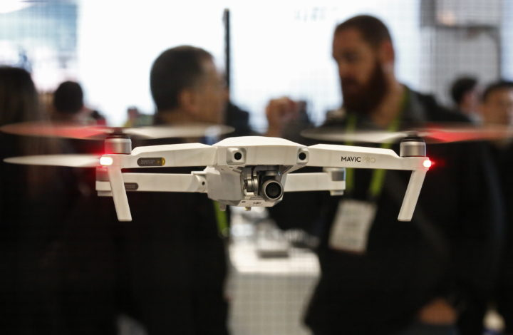 epa07962640 (FILE) - A DJI drone hovers while people watch on opening day at the 2018 International Consumer Electronics Show in Las Vegas, Nevada, USA, 09 January 2018 (reissued 31 October 2019). Reports on 31 October 2019 state the US Interior Department is stopping the usage of Chinese-made non-essential remote-controlled drones, saying 'drones manufactured in China or made from Chinese components' will be grounded except in emergencies and natural disasters. The department is in charge of the maintenance of federal lands in USA.  EPA/LARRY W. SMITH *** Local Caption *** 53998654